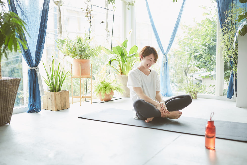 Mayo Uchida sitting on a yoga mat with the red WORKOUT bottle