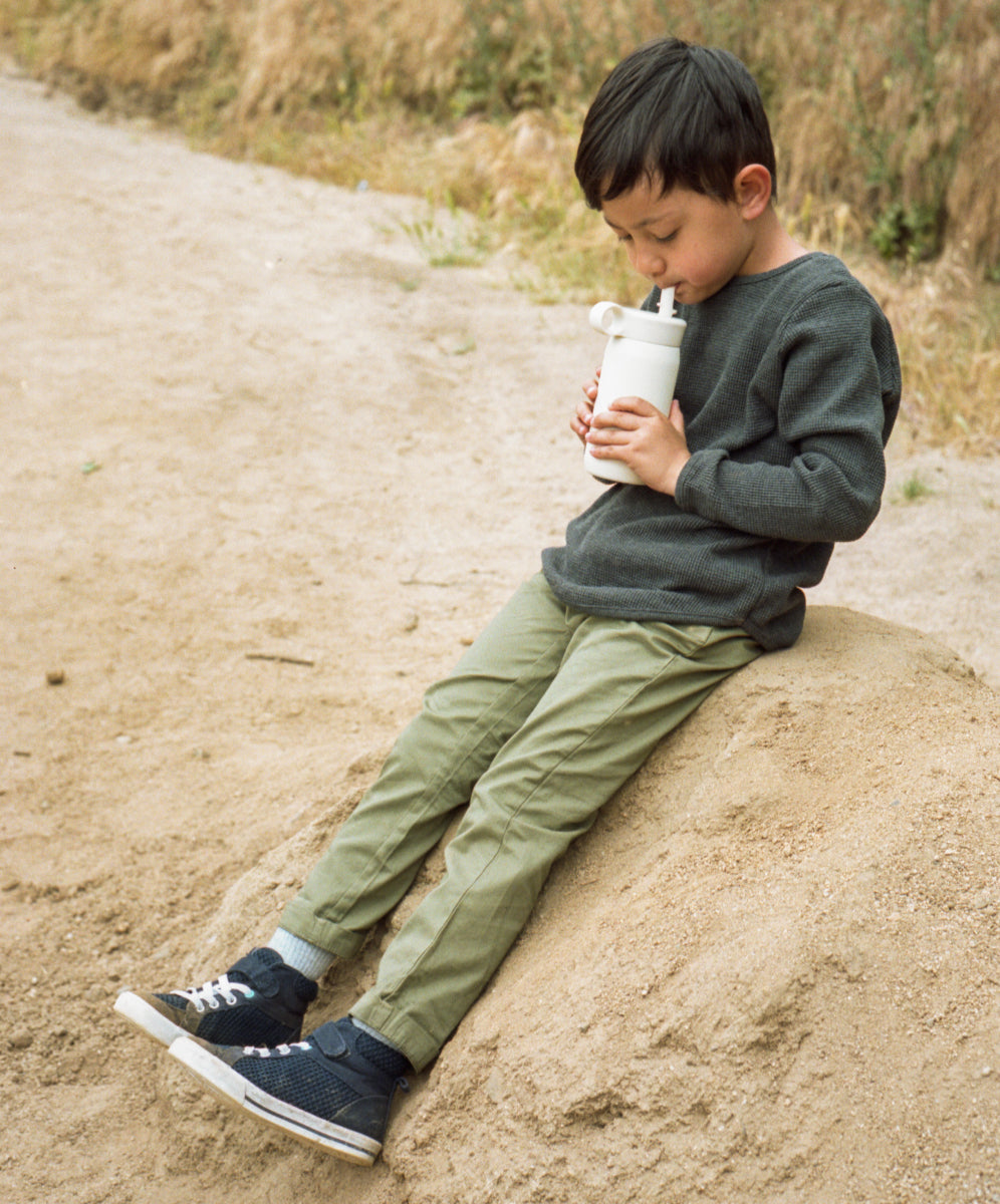 Boy sitting on a rock drinking from white PLAY tumbler