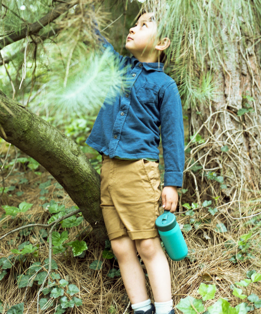 Boy holding PLAY tumbler while reaching up
