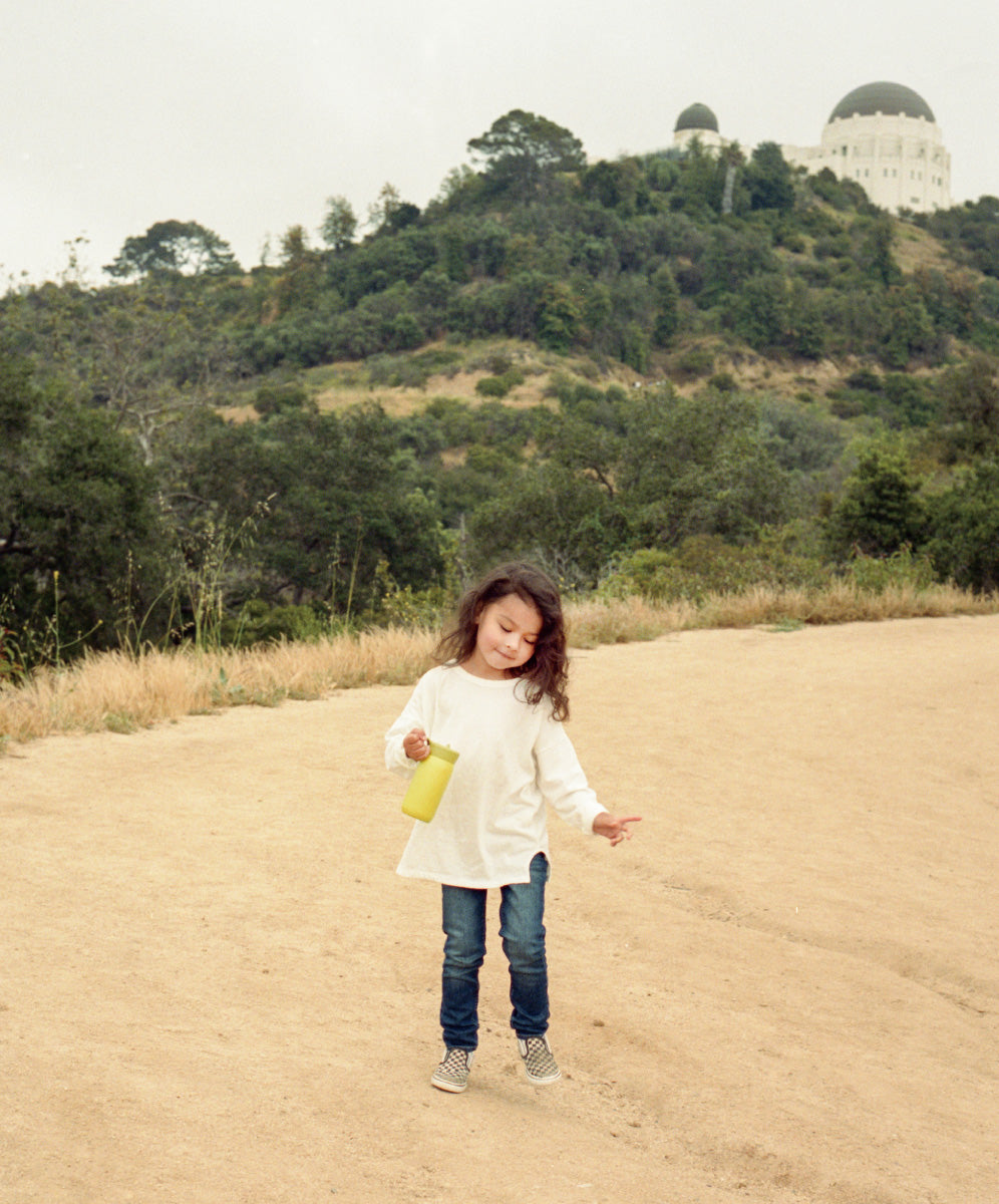Girl holding lime green PLAY tumbler on dirt path