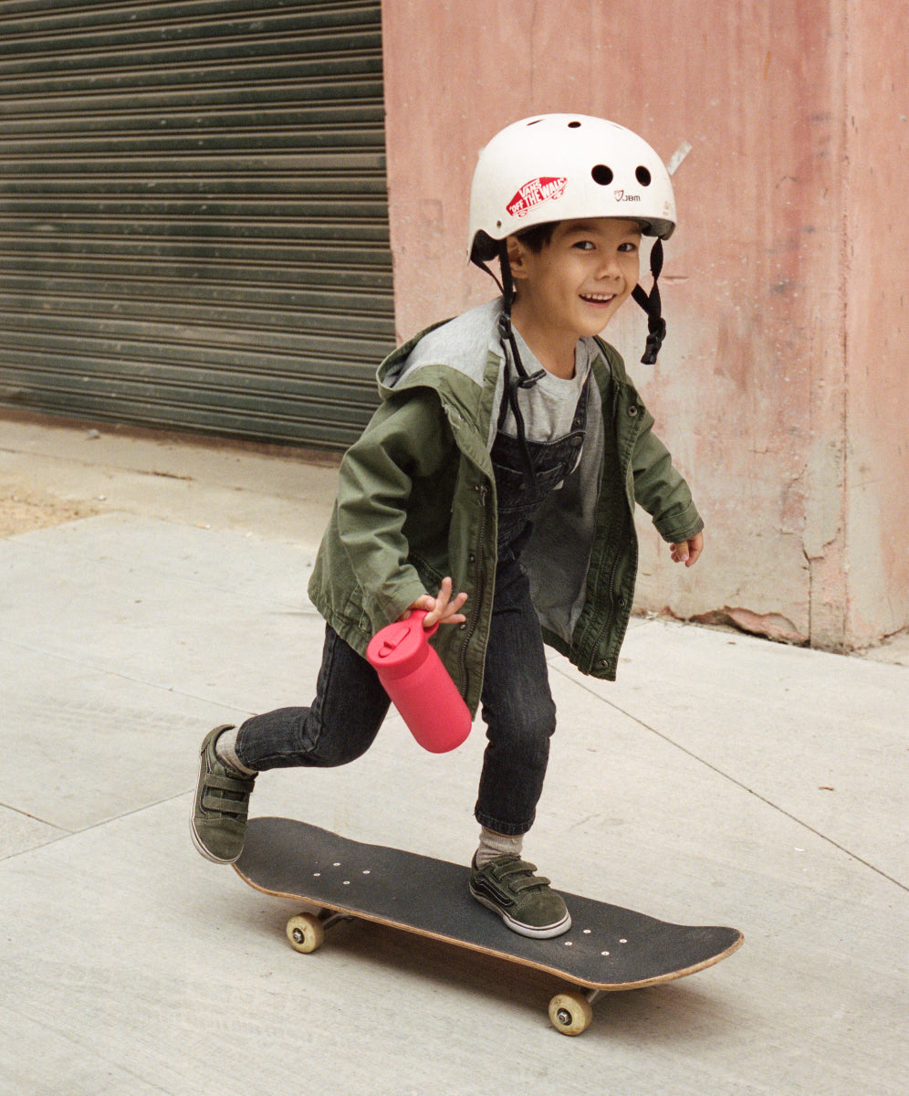 Boy skating with red PLAY tumbler