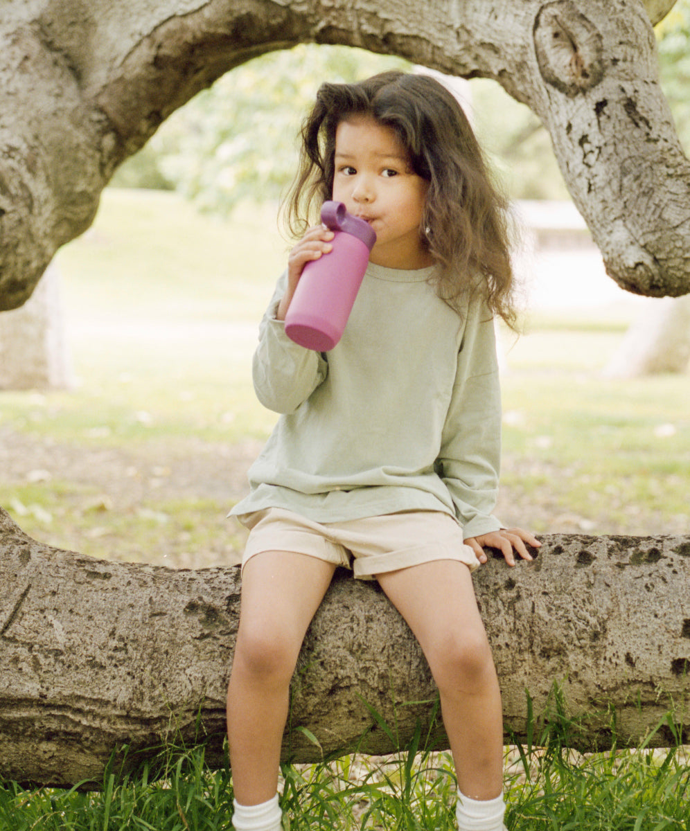 Girl sitting on a tree trunk drinking from a purple PLAY tumbler