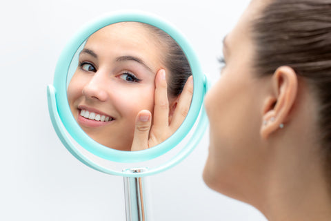 hifu facelift Toronto: woman looking in mirror, happy with hifu treatment results