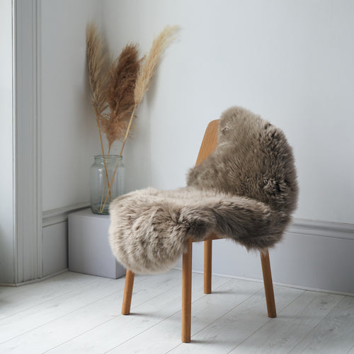 Ethically crafted  Sheepskin rug in Taupe draped over a chain