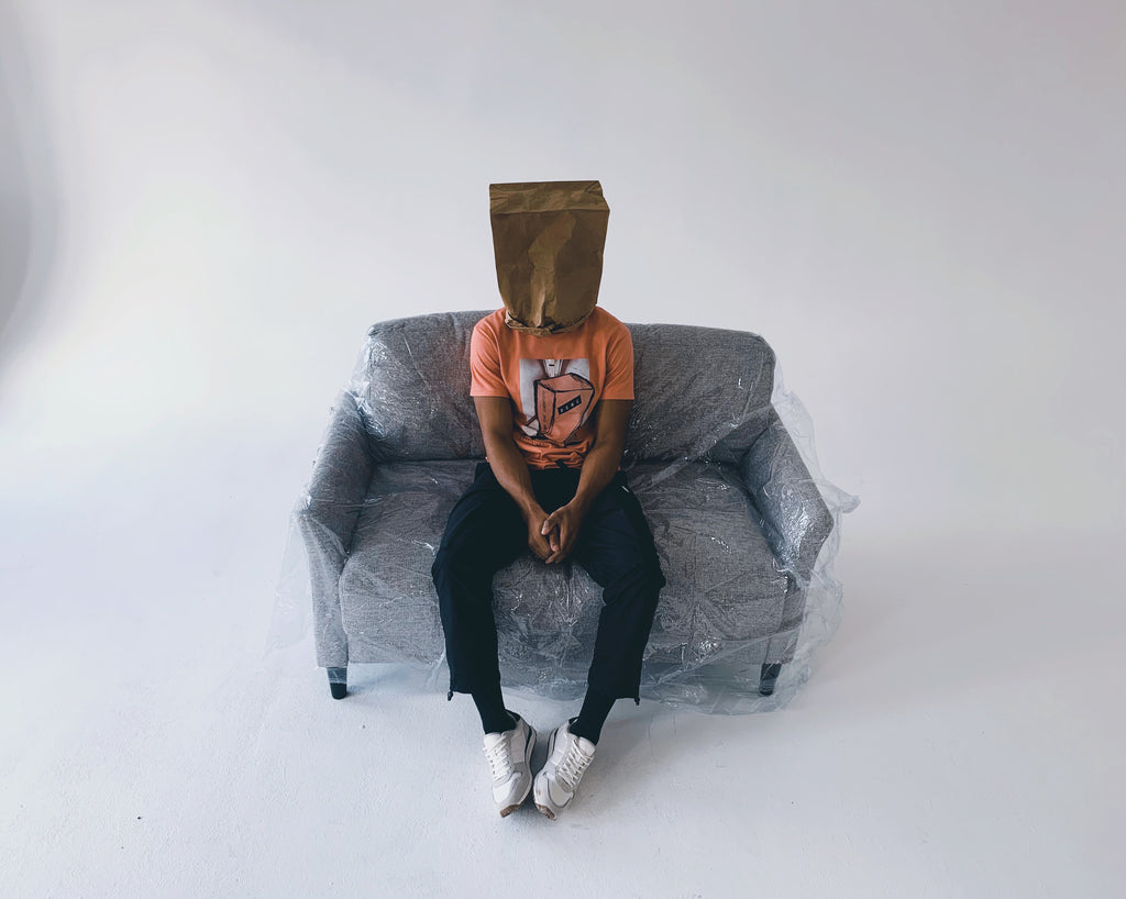 dsnc brooklyn, dsnc anti-conformity tee, dsnc class one tee, dsnc original content, man sitting on plastic covered couch, paper bag over head, wearing dsnc class one tee, wearing dsnc anti-conformity tee in terracotta, d