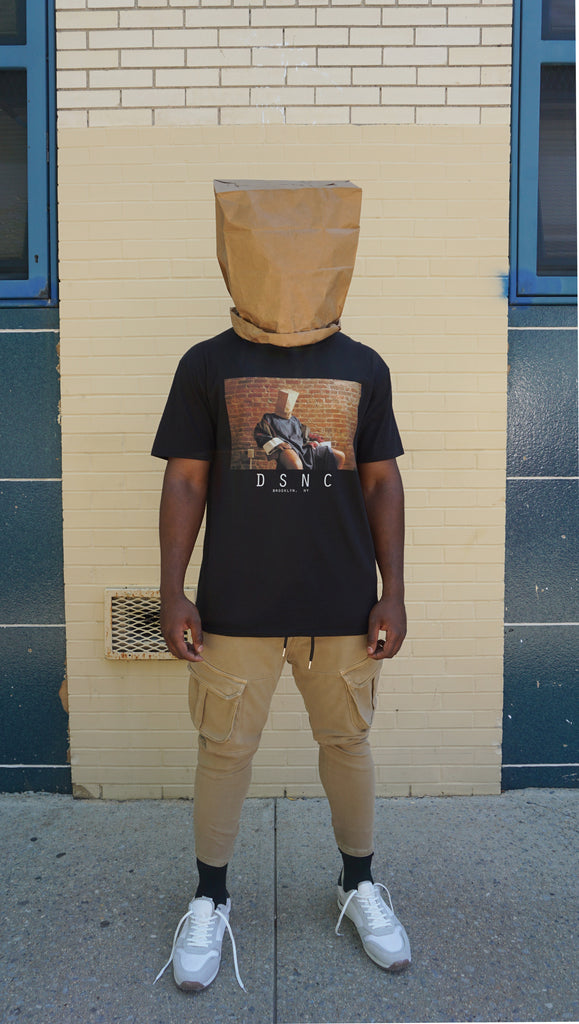 DSNC original pbg tee, black, full body, front side, classic fit t-shirt, graphic tee, printed photo of a person sitting in a chair, paper bag on the head, dsnc brooklyn, dsnc class one T-shirt.