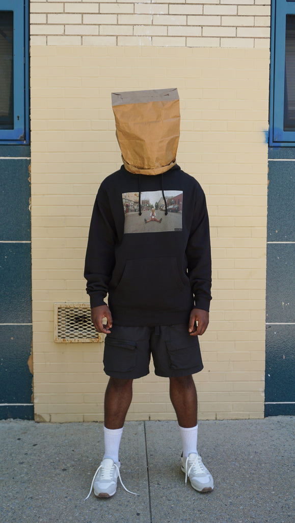 DSNC street minded hoodie,black, front side of the hoodie, black hoodie, graphic printed on front,printed photo of a person sitting in the street, paper bag on the head,, ribbed cuff and hem, dsnc brooklyn, dsnc class one hoodie, dsnc hoodie black, full body.