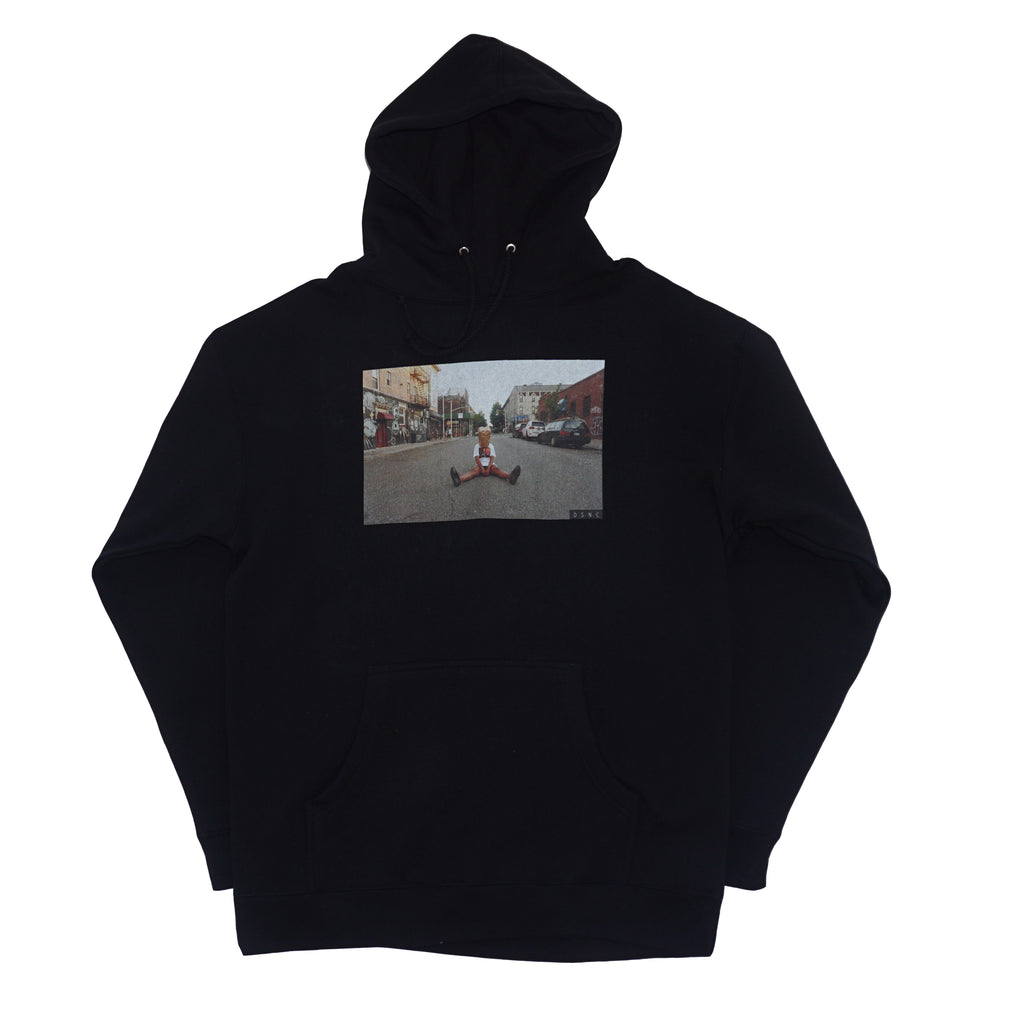 DSNC street minded hoodie,black, front side of the hoodie, black hoodie, graphic printed on front,printed photo of a person sitting in the street, paper bag on the head,, ribbed cuff and hem, dsnc brooklyn, dsnc class one hoodie, dsnc hoodie black.