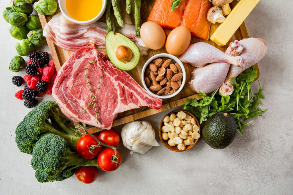 A spread of keto friendly foods including steak, nuts, avocado broccoli, berries, salmon, eggs, cheese, bacon, oils, and greens.