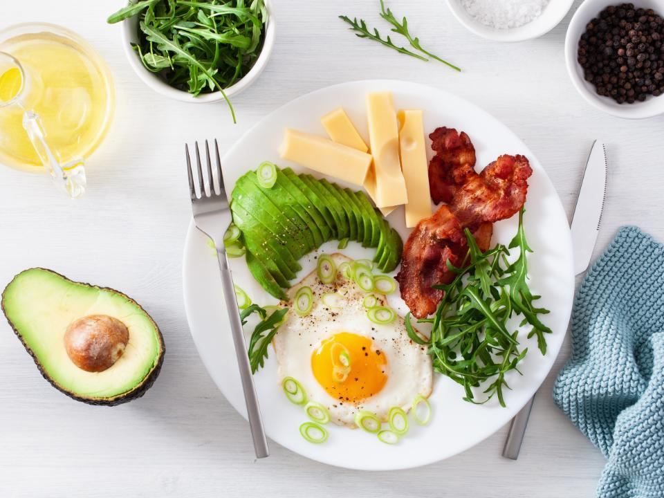 A plate of different keto foods, including avocado, eggs, bacon, cheese, and greens