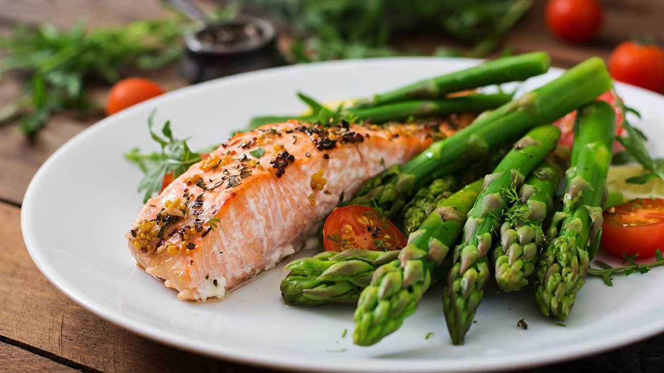 A plate of salmon and asparagus; both low carb foods.