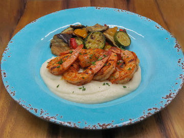 Grilled tail-on shrimp over cauliflower puree with a side of mixed grilled vegetables. Set on a blue plate on a brown cutting board.