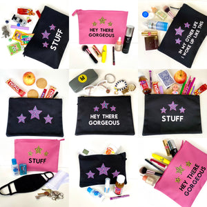Selection of nine accessory pouches in black and pink with various slogans, each holding different items