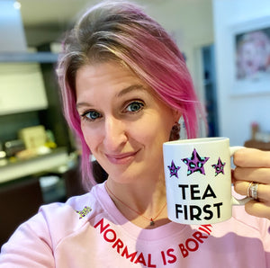 Woman with pink hair and pink slogan sweatshirt holding white ceramic mug with tea first slogan and leopard print pink and blue stars
