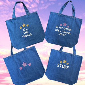 Four oversize denim shopper bags featuring slogans in white lettering and with three leopard print stars on each