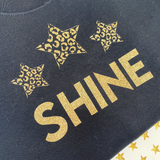 Close up of folded black Christmas sweatshirt with gold glitter Shine slogan and gold glitter leopard print stars