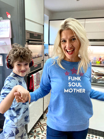 Blonde mum wearing light blue sweatshirt with white Funk Soul Mother slogan and pink leopard print stars, dancing with son in kitchen