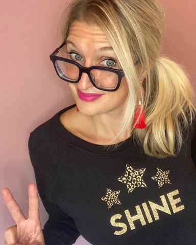 Black Christmas sweatshirt with gold glitter Shine slogan and gold glitter leopard print stars, blonde model with black glasses and red earrings
