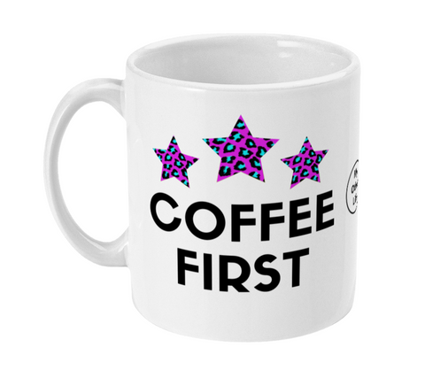 White ceramic mug with Coffee First slogan and three pink and blue leopard print stars