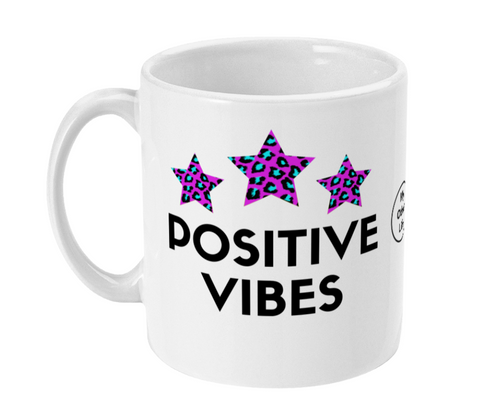 White ceramic mug with Positive Vibes slogan and three pink and blue leopard print stars