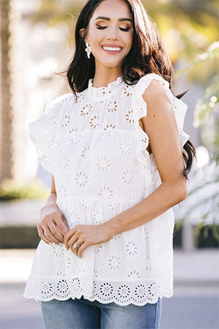 a woman wearing a precious intrigue white eyelet blouse and jeans
