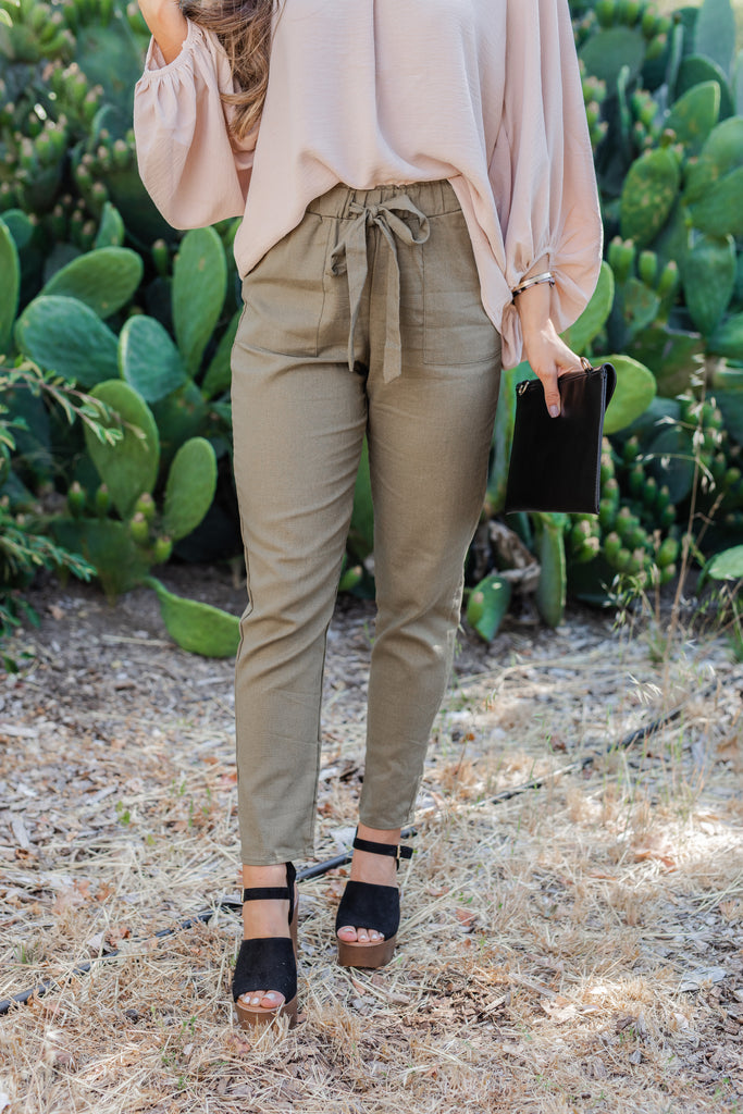 pants, bottoms, linen pants, paper bag waist pants, slim fit paper bag waist pants, slim fit paper bag waist pants with pockets, green slim fit paper bag waist pants with pockets, olive green tapered pants, tapered pants with pockets, tapered pants with paper bag waist, olive green tapered pants with paper bag waist and pockets, lightweight pants,