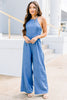 halter neckline, medium blue, sleeveless jumpsuit, pockets, wide leg hem