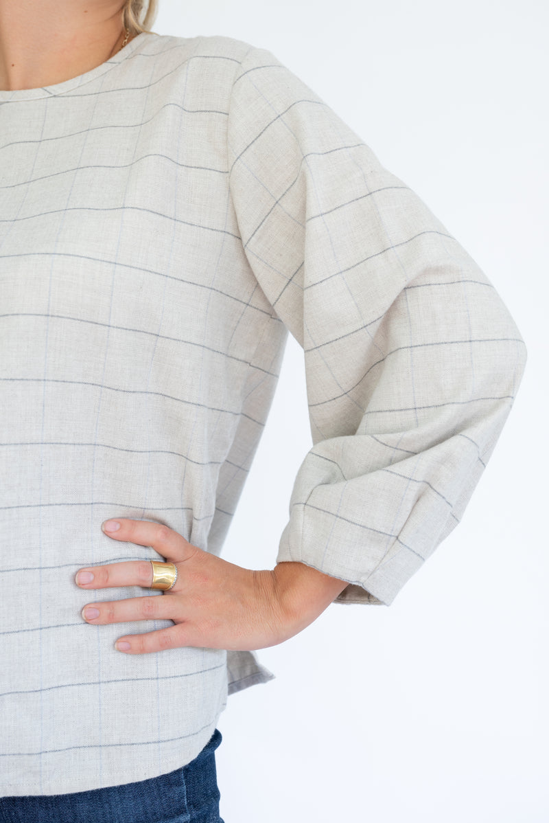 A closer view of the sleeve on Field Trip's balloon sleeve shirt. This is a limited-edition windowpane pattern for Fall 2020. Shown here with jeans and a gold ring on the model's middle finger.
