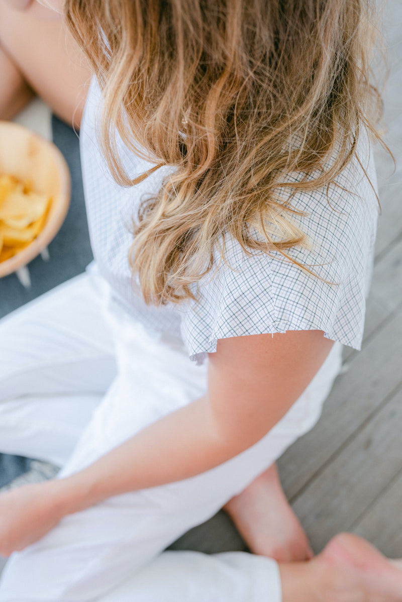 Field Trip's reversible flutter sleeve in a limited-edition sand dune check pattern for Spring 2021. Shown here tucked into white jeans. The model is having fish tacos and chips on a covered porch of a beach house.