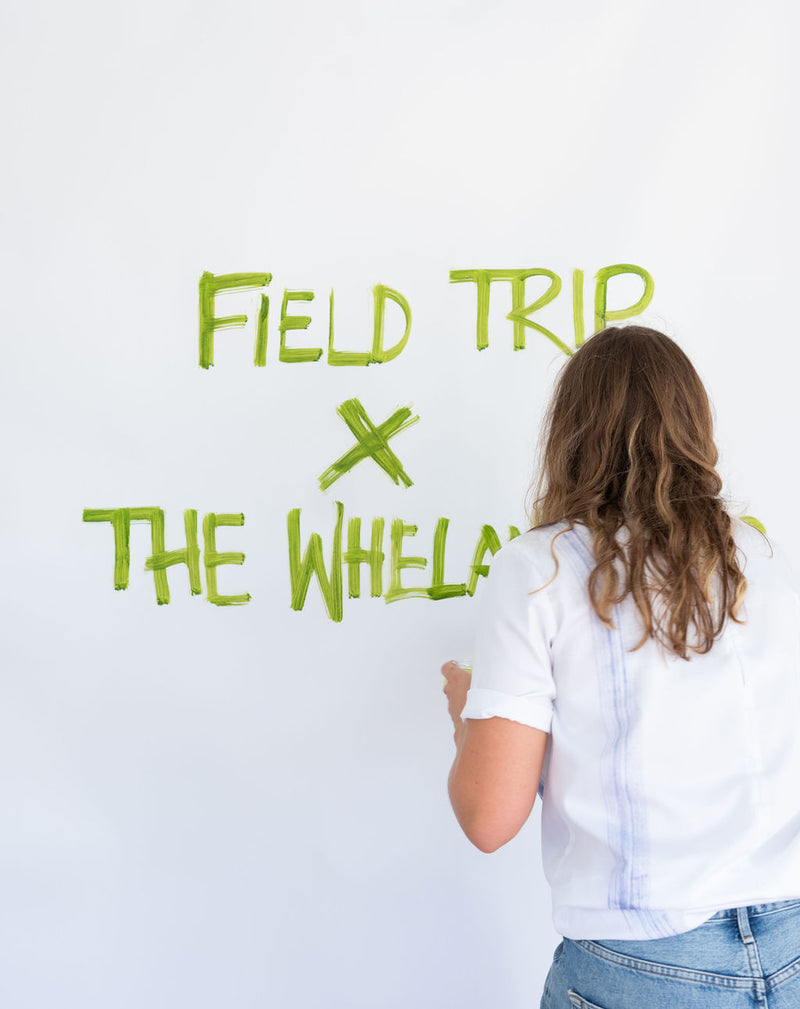 "Field Trip x The Whelan Girls collaboration. One of The Whelan Girls paints a sign  that reads, ""Field Trip x The Whelan Girls"" in green paint."