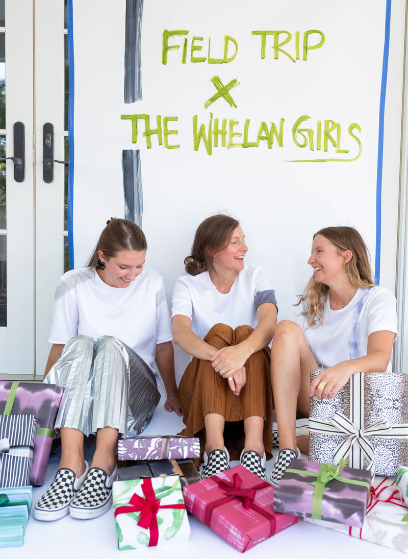 "Field Trip x The Whelan Girls collaboration. The Whelan Girls sit under a sign  that reads, ""Field Trip x The Whelan Girls"" with gifts wrapped in their brand's wrapping paper."