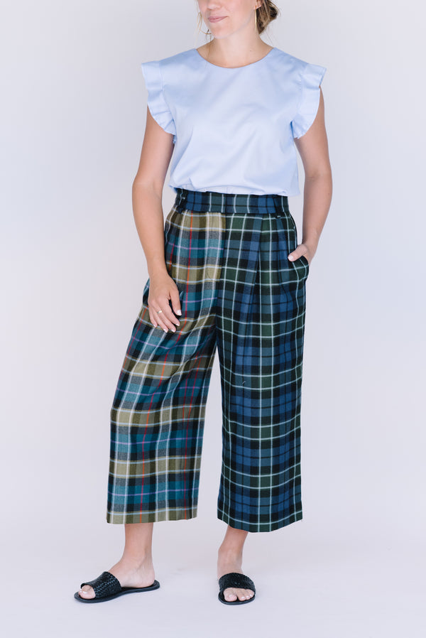 Field Trip's reversible flutter sleeve in light blue. Shown here with blue plaid pants and black leather slides.