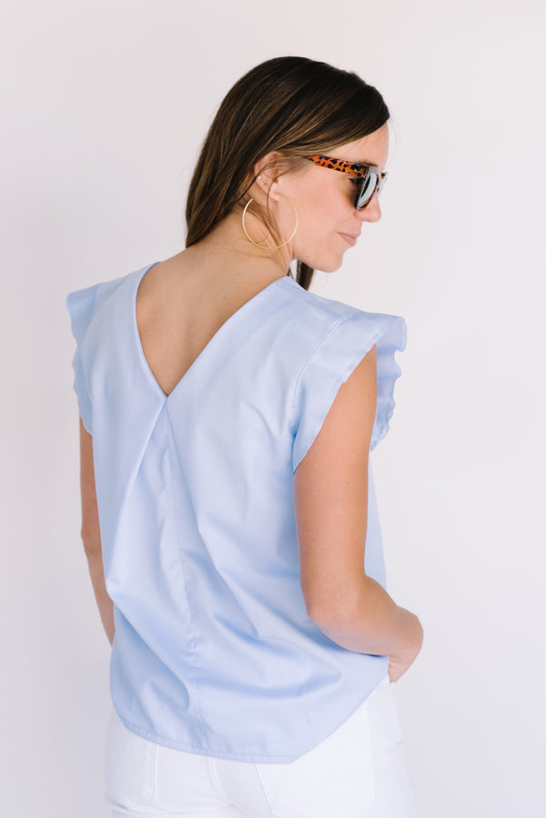 Back view of Field Trip's reversible flutter sleeve in light blue. Shown here with the V neck in back and worn with white jeans, tortoise shell sunglasses, and thin gold hoop earrings.