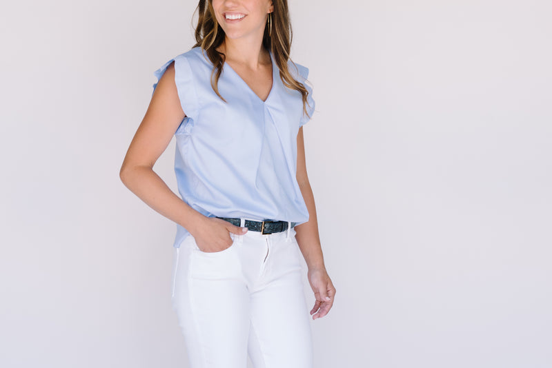 Field Trip's reversible flutter sleeve in light blue. Shown here with the V neck in front and worn tucked into white jeans with a blue and green leather belt.