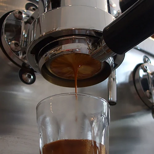 Extracting espresso from machine into latte glass.
