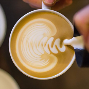 Barista pouring latte art rosetta into cup.