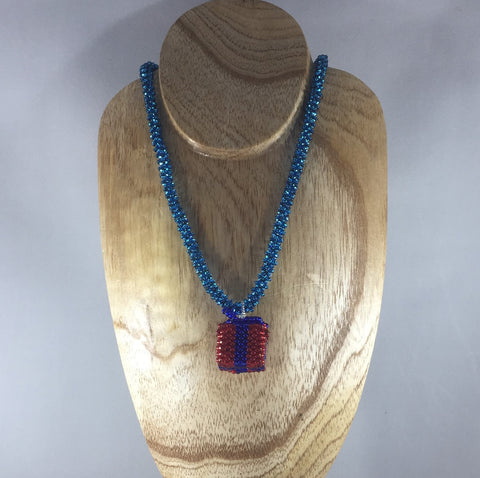 A small present box with a jingle bell inside dangling off a hand beaded rope.  Matching earrings included.  Necklace 16""