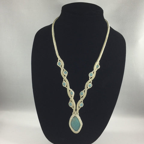 "Elegant Bead work encasing Turquoise pendant.  Necklace 24"" around.  Pendant 1.25"""