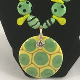 Necklace, Green striped and spotted ceramic and yellow duckbill beads