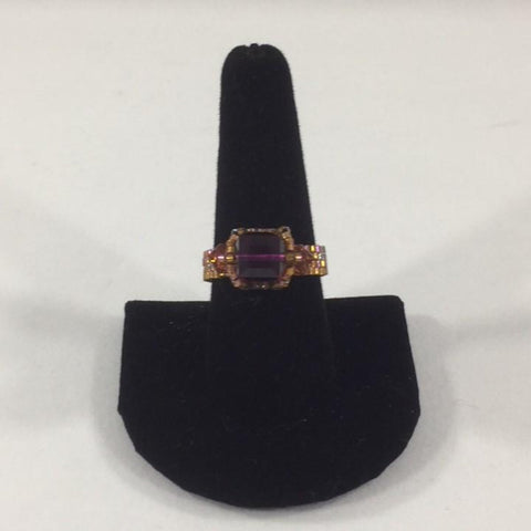 Amethyst Swarovski Cube Ring with 2 topaz accents.  Shimmer Gold Glass Seed Bead Band.  Size 9 1/2.  Although this ring is strung with Fireline, constant water exposure while wearing is not recommended.