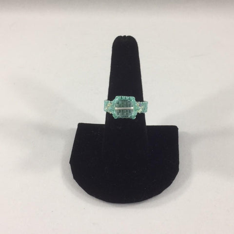 Beaded Ring with a Crystal Swarovski Cube and 2 Swarovski accents  Turquoise Glass Seed Bead Band.  Size 8.  Although this ring is strung with Fireline, constant water exposure while wearing is not recommended.