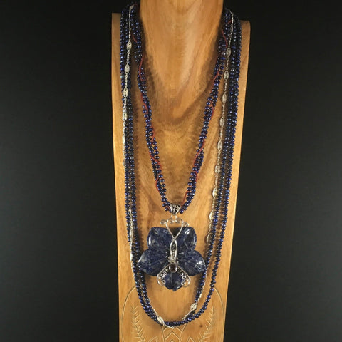 "Sterling necklace with four strands: two of Blue Lapis gems, one of Sterling Link Chain, one of Red Glass Seed Beads with a Blue Soladite and Sterling Butterfly Pendant.  Necklace 34""."