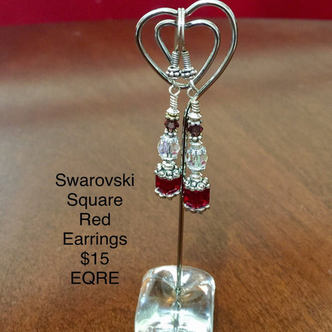 Pierced Earrings with a Red Swarovski Cube Bead, a Crystal Swarovski Round Bead and a Red Swarovski Bicone Bad. Sterling Silver findings and Ear Wires.