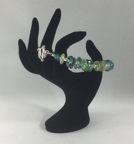 This stunning Greens and Blues bracelet is made up of all Lamp Work beads and Sterling Silver spacers.  Some of the Lamp Work beads have Frit on them.  The clasp is also Sterling Silver.  Size 8.25