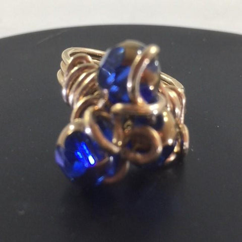 Gold tone Wire Wrap Ring with 3 Blue Cathedral Beads wrapped around swirls of ire.  Size 7 1/4