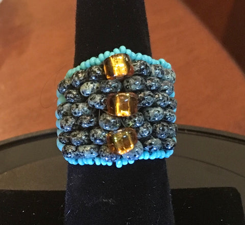 Beaded, Turquoise, Gray mottled and Gold accent Beads.  Size 7.  Although this ring was strung with Fireline, constant exposure to water is not recommended.