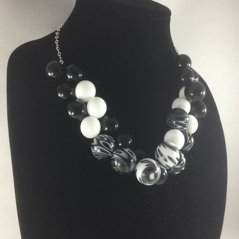 "Hand Blown Glass Bead necklace with Sterling chain.  These beads were hand-blown by Anna Scherbakova who lives in Russia. She used black and white rods to create each glass ball.  Then the balls were kiln annealed for hardness and finished with a dremel.  The necklace measures 18""."