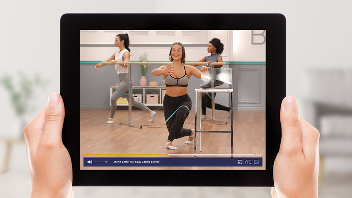 Tablet showing a group barre workout class with a trainer holding onto a chair.