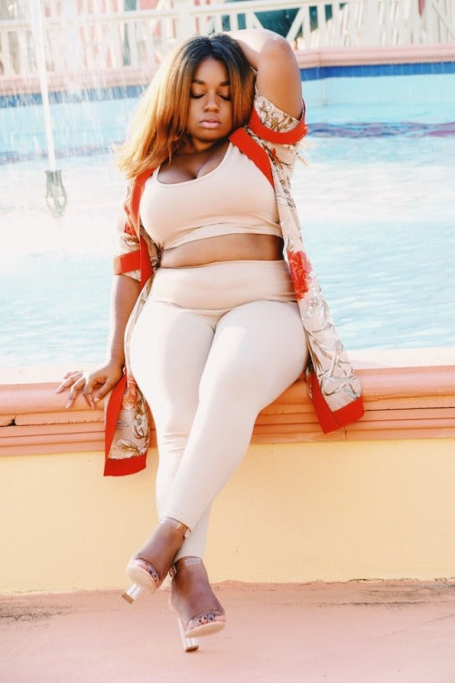 plus size lady rocking a white top, white trousers and a red sweater