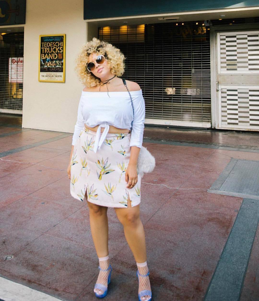 plus size lady wearing a floral dress, white top and shoes